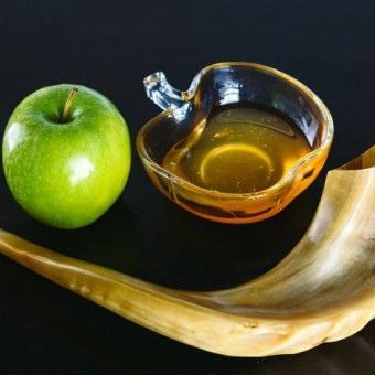 Whole green Apple sitting next to a glass bowl with golden honey. Both are sitting with the curve of a shofar or ram's horn used to call Jews to worship on Rosh Hashanah