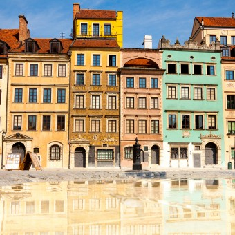 Morning in Warsaw Poland. A block of multi-level apartment buildings with red roofs set against a blue sky