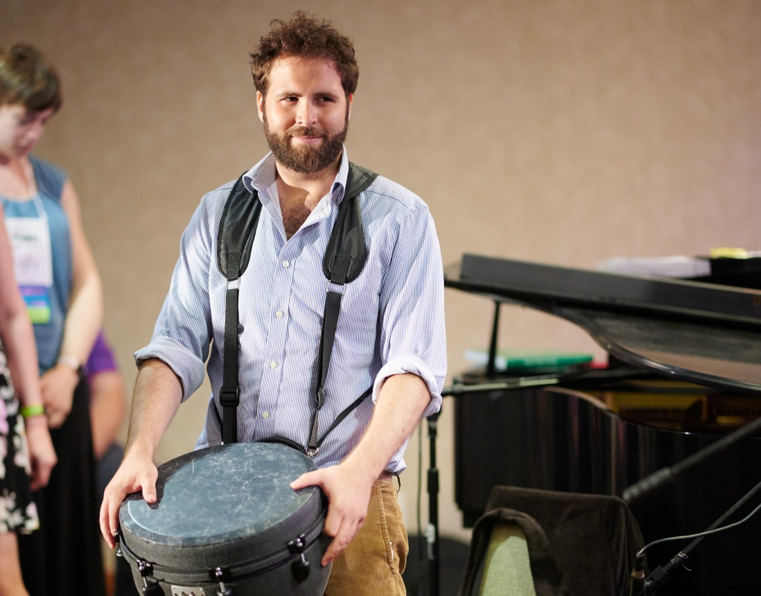 Cantor Tobias Glazer playing a drum hanging from his neck