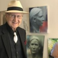 Cantor Sheldon Merel, wearing a black shirt, white tie, and hat standing in front of photos and painting