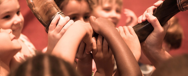 Children's hands grasping a shofar
